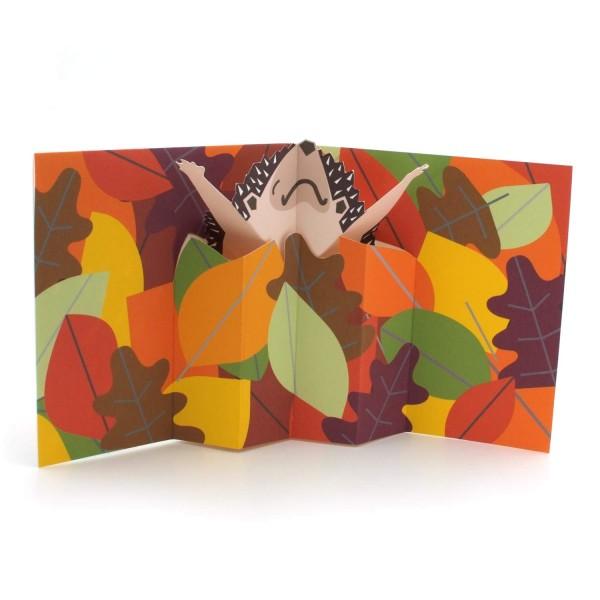 Pop-up-Karte mit einem sich reckenden Igel in einem Laubhaufen
